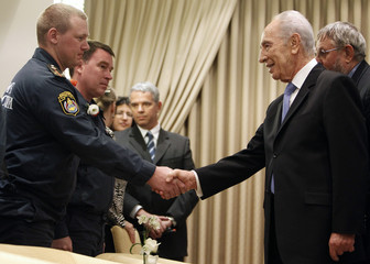Israel's President Peres shakes hands with a member of a Russian delegation in Jerusalem