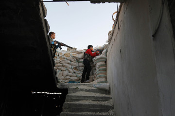 Abboud and his brother Deeb stand with their weapons behind sandbags in Aleppo