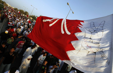 People shout anti-government slogans as they wave a huge Bahrain flag with freedom symbols during a rally held by the main opposition al-Wefaq party in Budaiya