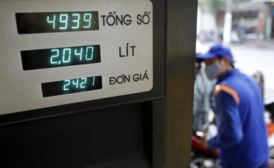 A man pumps petrol into a motorcycle at a petrol station in Hanoi