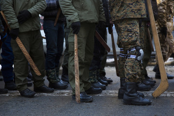 Members of various anti-government paramilitary groups walk in formation during a show of force in Kiev