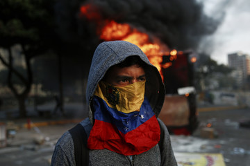 An anti-government protester walks next to a burning kiosk during a protest at Altamira square in Caracas