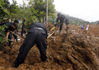 Rescue workers conduct a search at the site of a landslide at the Koslanda tea plantation near Haldummulla