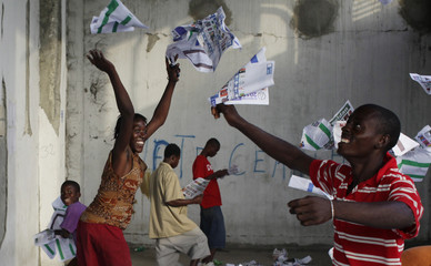 Haitians throw ballots into the air after frustrated voters destroy electoral material during a protest in a voting center in Port-au-Prince