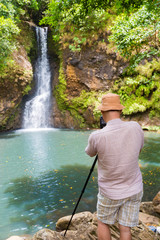 Photographer taking photo of Chamouze waterfall. Mauritius