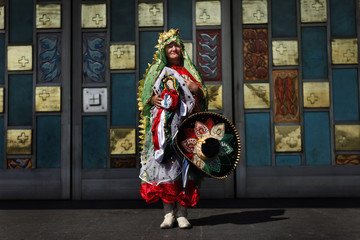 A pilgrim dressed as the Virgin of Guadalupe poses for a photo as she holds a charro hat at Basilica's square in Mexico City