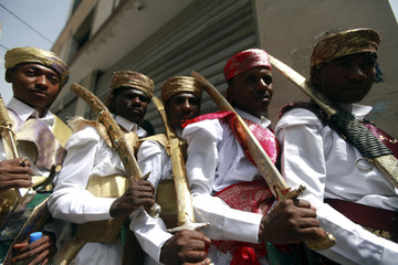 Grooms, who are employees of the Secretariat of the capital Sanaa, pose for pictures wearing traditional costumes and carrying swords for a mass wedding ceremony in Sanaa