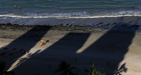 An ice cream vendor pushes his cart on the Boa Viagem beach in the northeastern Brazilian state of Recife
