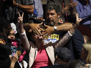 A convention attendee covers the face of Alli McCracken of Code Pink as she shouts during a protest at the Republican National Convention in Cleveland