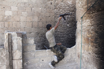 A Free Syrian Army fighter shoots his weapon in the old city of Aleppo