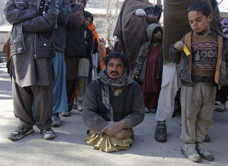 A man waits in line to receive aid donated by the Turkish government in Kabul