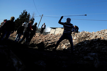 A Palestinian protester uses a sling to hurl stones towards Israeli troops during clashes following a protest against the near-by Jewish settlement of Qadomem, in the West Bank village of Kofr Qadom
