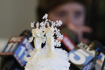 Wedding cake toppers are pictured as Robin Tyler cries in the background at a news conference in Los Angeles