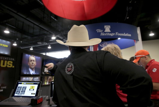 A man wearing a cowboy hat stops at the booth for the National Rifle Association (NRA) at the 2016 Conservative Political Action Conference (CPAC) at National Harbor