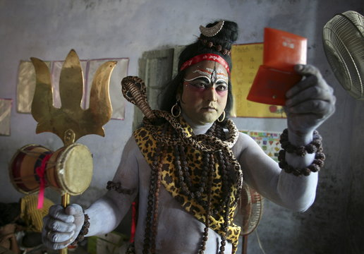 A man dressed as Hindu Lord Shiva looks into the mirror as he gets ready to take part in a religious procession in Amritsar