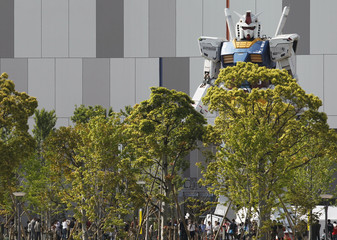 "Full-size model of Japan's robot animation character ""Gundam"" stands in front of a shopping mall behind trees in Tokyo"