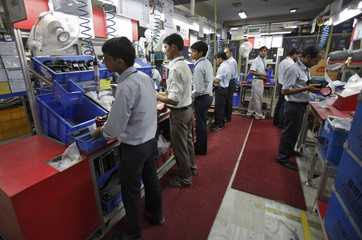 Employees work at the factory of the Samvardhana Motherson Group in Noida