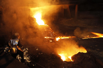 A worker checks molten cast iron in front of the furnace at Turkish steel manufacturer ISDEMIR in Iskenderun in Hatay province