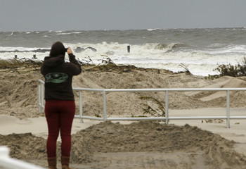 An onlooker photographs the rough surf near the seawall along Beach Avenue in Cape May