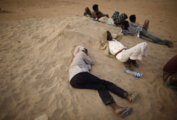 Ethiopian migrants rest outside a transit center where they are waiting to be repatriated in the western Yemeni town of Haradh on the border with Saudi Arabia