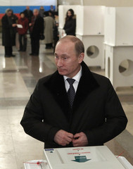 Russia's PM Putin looks on after casting his ballot at a polling station during the parliamentary election in Moscow
