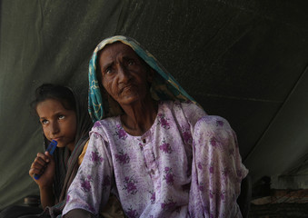 Woman displaced by flooding waits for relief along with her grand daughter near the flooded village of Bello Patan