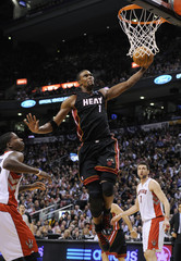 Miami Heat Bosh goes up for a slam dunk past Toronto Raptors during the first half of their NBA basketball game in Toronto