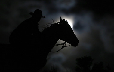"Wrangler Nate Cummins takes the opportunity to ride by moonlight, the night before the ""Super Moon"" during Montana Horses' annual horse drive outside Three Forks"