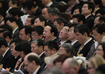 A delegate yawns during the opening ceremony of the NPC at the Great Hall of the People in Beijing