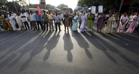 Activists from SUCI block a road during a protest against a recent hike in petrol prices in Kolkata