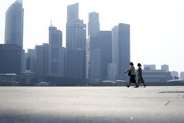 People walk past the skyline of the financial district on a hazy day in Singapore