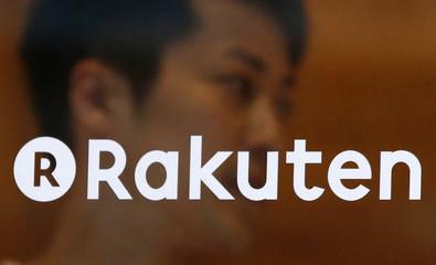 A staff of Rakuten Cafe is seen behind a logo of Rakuten Inc. in Tokyo