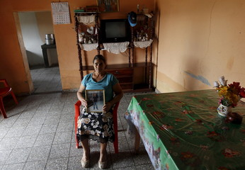 Ana Rodas holds a picture of her son who disappeared during his journey through Mexico to reach the U.S,  at the town of the Ermita outside Tegucigalpa.