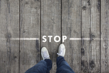 Fototapeta Man standing on the wooden boards with stop message on the floor, point of view perspective used. obraz