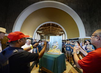 People take photographs of a birthday cake in celebration of Union Station's 75th anniversary during a rededication ceremony coinciding with Amtrak's own national Train Day at Union Station in Los Angeles