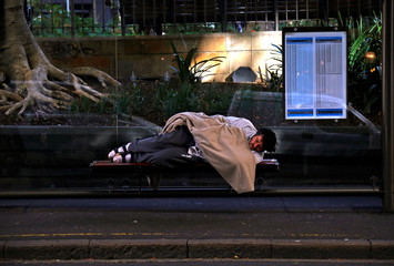 A man covers himself with a blanket as he lies on a seat at a bus terminal in the central business district of Sydney
