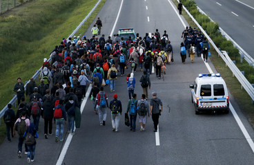 Hungarian police escorts a group of migrants walking against the traffic on a motorway leading to Budapest as they left a transit camp in the village of Roszke
