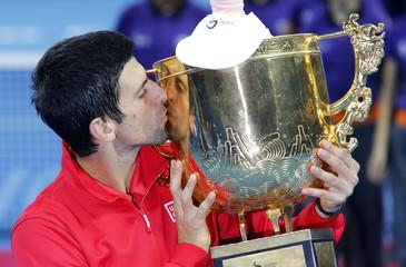 Novak Djokovic of Serbia kisses the trophy after winning his men's singles final match against Rafael Nadal of Spain in Beijing