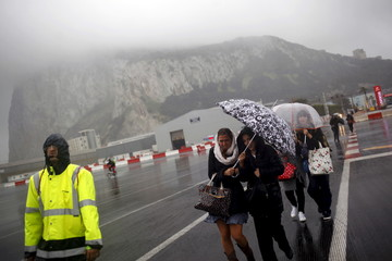 Pedestrians cross the tarmac of the Gibraltar International Airport during heavy rain in front of the Rock of the British colony of Gibraltar