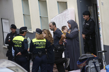 Bendjazia speaks with police officers after being evicted from their rental flat in Madrid