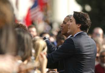 U.S. President Obama and Canadian Prime Minister Trudeau greet audience during arrival ceremony at the White House in Washington