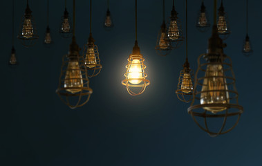 Hanging retro light bulbs decor on dark blue background with one isolated glowing .