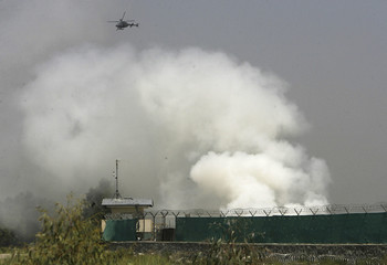 A NATO helicopter flies above the scene of a raid as smoke rises from a base in Jalalabad