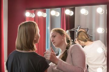 Make-up artist doing the make-up for girl