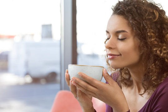 Good morning world! Closeup shot of a young African woman enjoying a cup of coffee smiling with her eyes closed