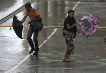 A man and a woman stuggle to hold their umbrellas from high wind and rain during a wet day in Colombo, Sri Lanka