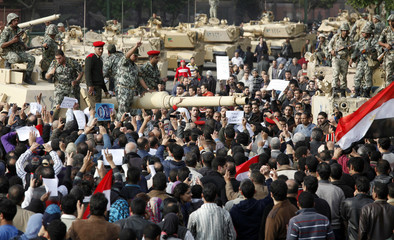 A crowd gathers around Egyptian Army soldiers standing on top of a tank in Cairo