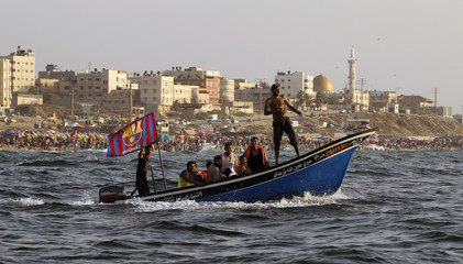 Palestinians ride a boat as they enjoy the warm weather on a Gaza City beach