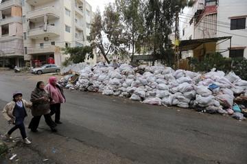 Residents walk near packed garbage in Wadi al-Zayneh, Chouf district