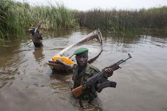 Rangers prepare to destroy a boat belonging to two men who were fishing illegally in the protected waters of Virunga National Park in eastern Congo